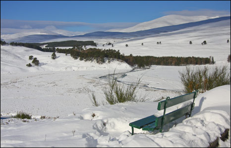 Bench on snowy hill top