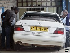 Kenyan students look at the car in which Oscar Kamau Kingara and his colleague were shot dead, 6 March