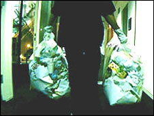 Person carrying rubbish bags