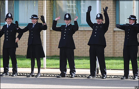 Police recruits perform a Mexican wave.