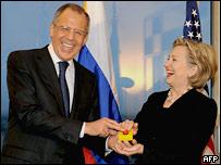 Министр иностранных дел России Сергей Лавров и госсекретарь США Хиллари Клинтон смеются над ошибочной надписью на подарке в Женеве