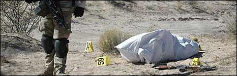 A Mexican soldier with a body in Villa Ahumada, about 120km south of the border between Ciudad Juarez and El Paso