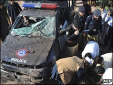 Policemen inspect a police van hit by an explosion which killed eight on the outskirts of Peshawar, Pakistan on 7 March