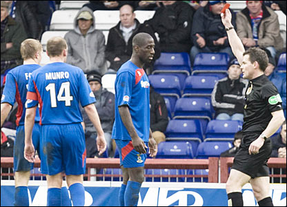 Lionel Djebi-Zadi (centre) is shown the red card by referee Steve Conroy for his challenge on Carl Finnigan