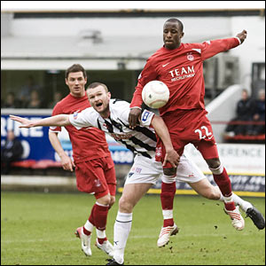 Dunfermline's Scott Wilson (left) is shrugged off by Sone Aluko