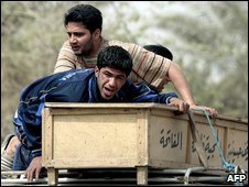An Iraqi man (front) mourns over the coffin of his brother, who was killed in a suicide attack in Baghdad on Sunday
