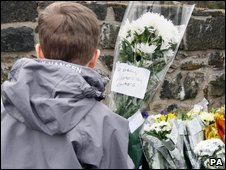 A young boy leaves flowers outside the army base in Antrim, Northern Ireland