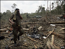 Ecuadorian soldier examines remains of rebel camp attacked by Colombia troops (3.3.2008)