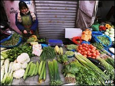 A woman sells vegetables in China's Anhui province