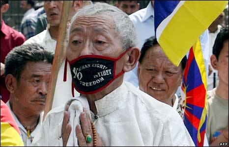 An elderly Tibetan man prays during a protest march in Delhi, India