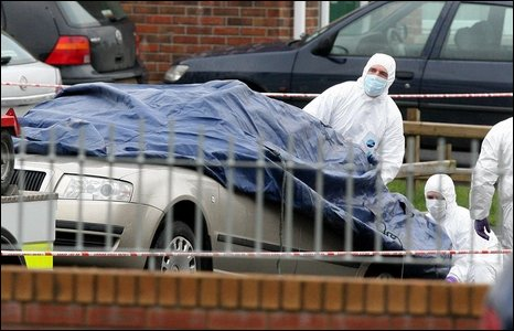 The car in which Constable Carroll was fatally wounded is covered with a tarpaulin and towed away by forensic experts for more detailed examination.