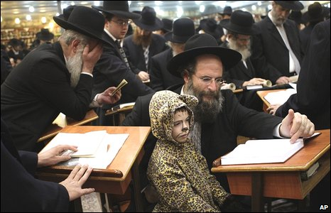 Israeli Jewish Orthodox men and a child in costume, read a Scroll of Esther which tells the story of the Jewish festival of Purim in the town of Beni Brak, on the outskirts of Tel Aviv, Israel