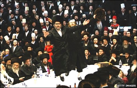 Ultra-Orthodox Jews belonging to the Vishnitz Hassidic sect dance on their Rabbi's table as they celebrate the Jewish festival of Purim in Bnei Brak, a religious town near Tel Aviv in central Israel