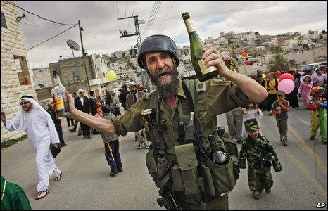 A seemingly inebriated Jewish settler dressed as a soldier dances with others during an annual parade marking the Jewish holiday of Purim as they walk through a Palestinian area in the divided West Bank town of Hebron
