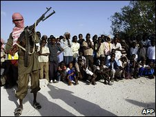 A Somali Islamist fighter stands guard over a crowd that gathered to watch the public flogging of teenage boys convicted of raping a minor in Mogadishu, Somalia, on 9 March 2009