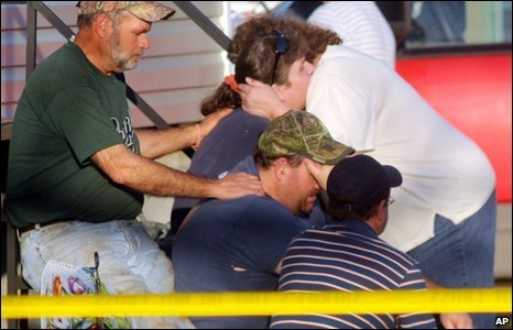 Residents comfort each other at the scene of a shooting in Samson, Alabama, on 10 March, 2009
