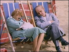 Two people in deckchairs on the beach