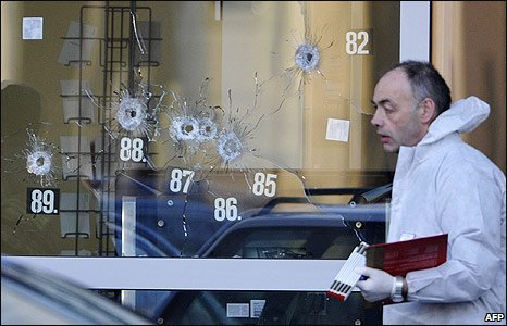 A police officer walks past bullet holes in a window at Albertville school in Winnenden, Germany