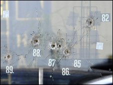 A window with bullet holes is numbered at the scene at a car showroom in Wendlingen, Germany, 11 March 2009