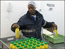 Worker packing bottles of Blue Skies fruit juice, Ghana