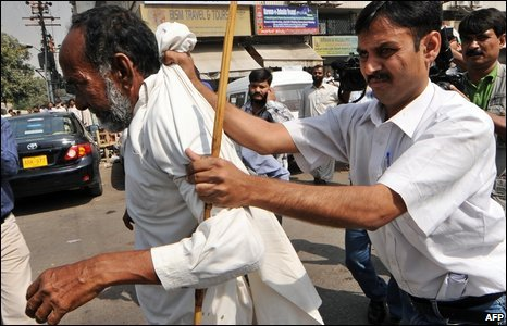 A Pakistani policeman arrests a Jamaat-i-Islami supporter during a protest in Karachi on March 12, 2009
