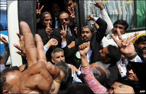 Pakistani lawyers in Karachi make victory signs as they board a bus for Islamabad on 12 March, 2009