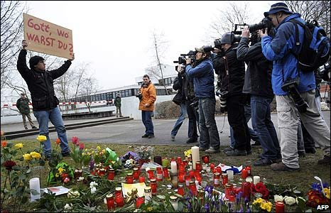 """A man holds a sign saying """"God where were you?"""" outside Albertville school in Winnenden, Germany"""