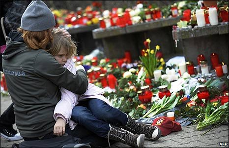 A woman and child sit by a tribute at Albertville school in Winnenden, Germany