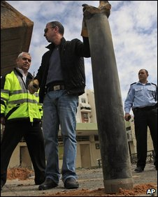 Israeli police officers examine the remains of a rocket fired by Palestinian militants in Gaza