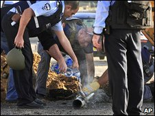 Israel police douse a recently landed rocket fired from Gaza in Ashkelon, 3 February