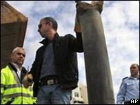 شرطي إسرائيلي يعاين آثار قذيفة فلسطينية