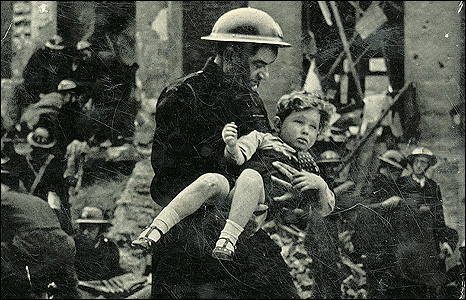 Fireman John Stewart carrying a child from a bombed building