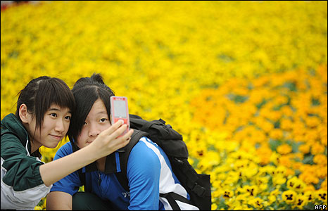 Two girls take pictures of themselves with one of the displays at the Hong Kong Flower Show