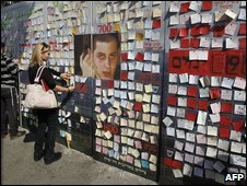 Isralis post notes of support on a wall next to a picture of Sgt Shalit, 12/03