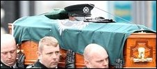 The coffin containing PC Carroll is carried to the church by police officers. His widow, Kate, is seen on the left.
