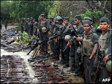 Sri Lankan troops stand beside captured weapons and the bodies of dead Tiger fighters, 10 March