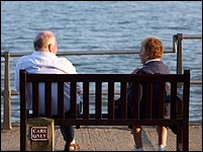 An elderly couple on a bench by the beach