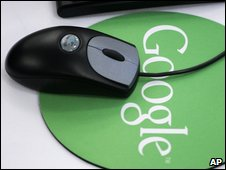 A computer mouse sitting on a Google mouse mat