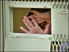 A Guantanamo detainee peers through his hands from inside his cell (File picture)