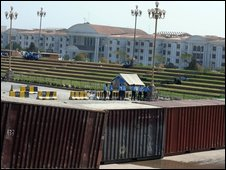 Police-men are deployed at container barricades erected by the authorities in front of President House in Islamabad on March 14, 2009