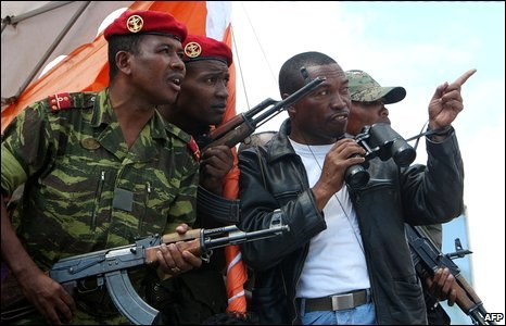 Men in military uniform listen to an address by opposition leader Andry Rajoelina at a rally in Antananarivo, 14 March 2009