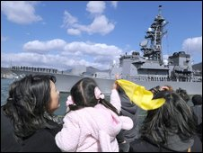 Family members wave as a destroyer leaves the naval port in Kure city in Hiroshima prefecture, 14 March