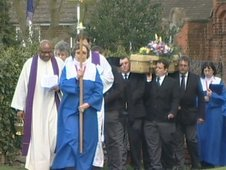 The coffin being carried from the church to the graveyard