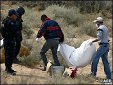 Mexican police carry body found partially buried in desert near Ciudad Juarez - 14/3/2009