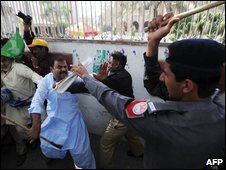 Pakistani policemen baton charge supporters of former premier Nawaz Sharif during an anti-government protest rally in Lahore on 15 March 2009