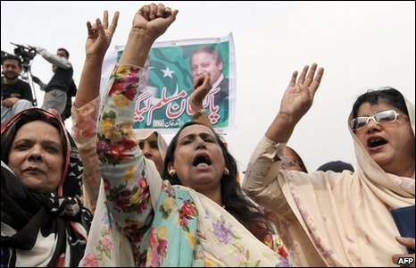Women raise their hands in victory in Islamabad, Pakistan