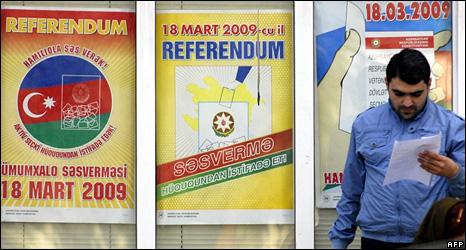 Man walks past referendum posters in Baku