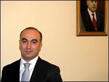 Elnur Aslanov stands next to a portrait of Haydar Aliyev