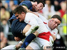 England's Toby Flood (L) and Joe Worsley (R) tackle Julien Malzieu of France