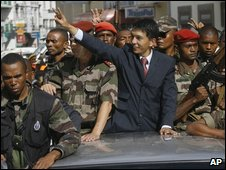 Andry Rajoelina parades through the narrow streets of Antananarivo, Madagascar standing on a vehicle surrounded by soldiers